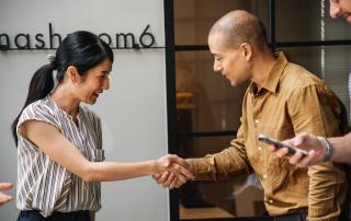 Aperto de mão entre homem e mulher em ambiente de trabalho